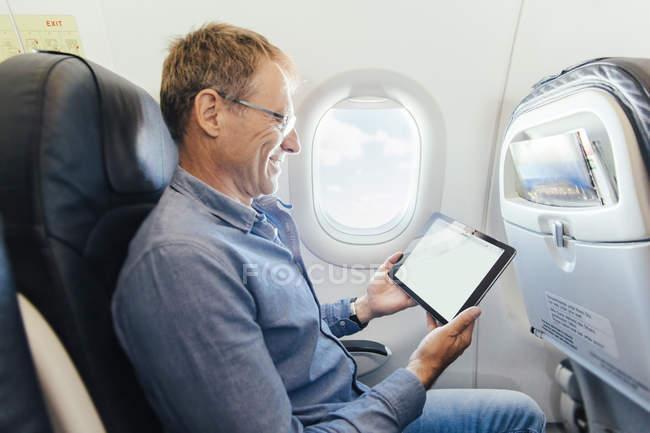 Uomo maturo seduto su un aereo a guardare il suo tablet digitale — Foto stock