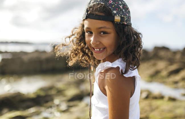 Портрет улыбающейся маленькой девочки на скалистом побережье — стоковое фото