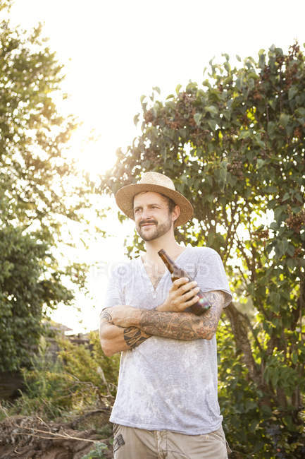 Portrait of man with tattoos on his arms standing in the garden holding bottle of beer — Stock Photo