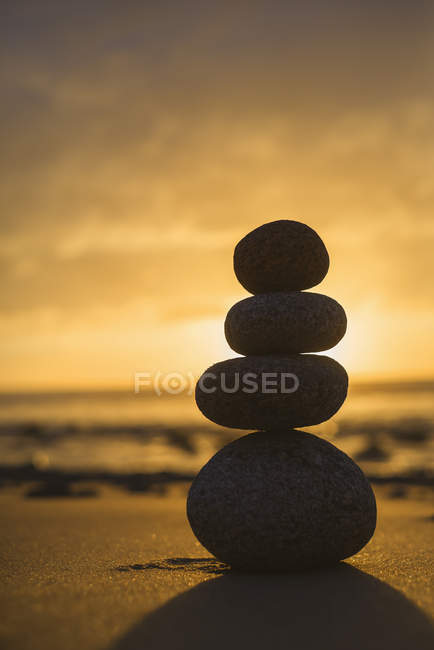 Spain, Valdovino, four stones in balance on the beach at backlight — Stock Photo