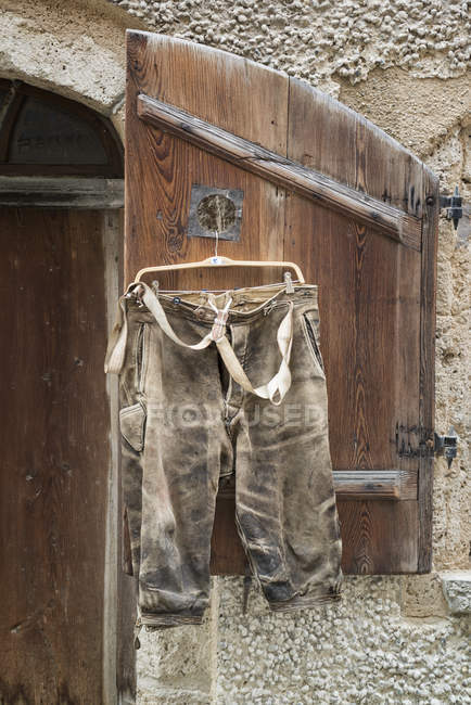 Short leather trousers hanging on shutter for sale — Stock Photo