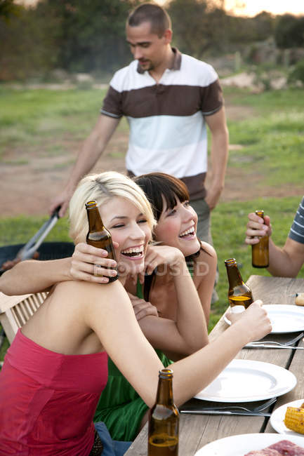 Happy friends embracing at garden table on a barbecue with beer bottles — Stock Photo