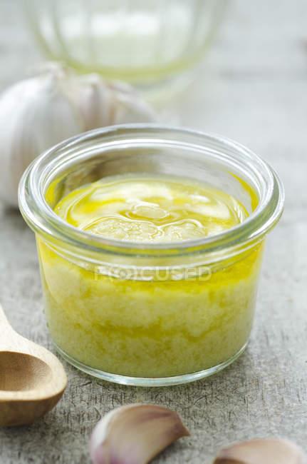 L'ail maison coller avec de l'huile dans le récipient avec l'ingrédient — Photo de stock