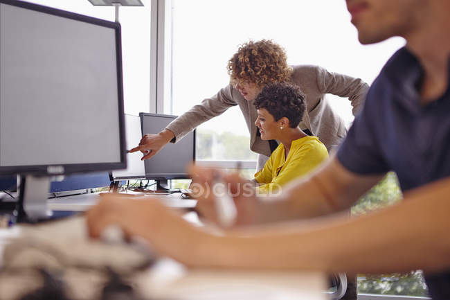 Young man pointing at colleague's computer screen — Stock Photo