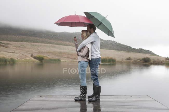 Couple debout sous la pluie sur une promenade en bois avec parasols — Photo de stock