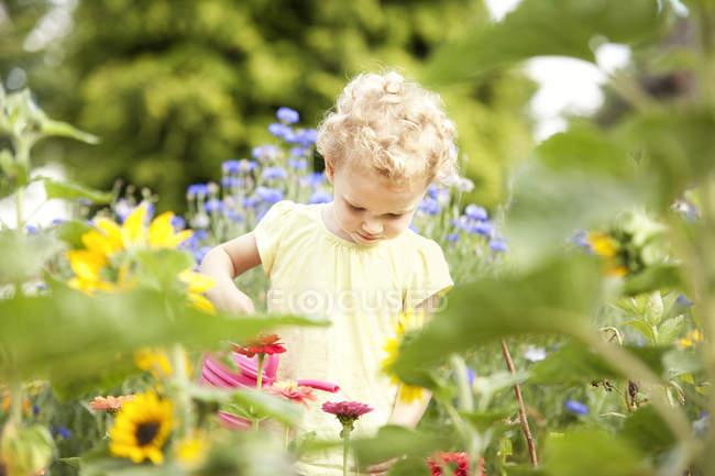 Petite fille debout dans le jardin arrosant des fleurs — Photo de stock
