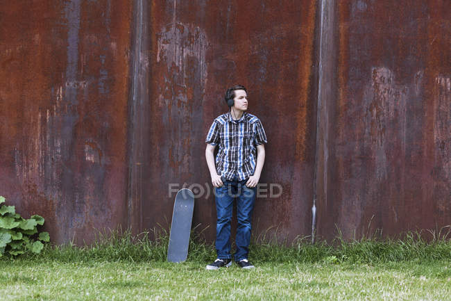 Teenage boy with skateboard leaning on corten wall hearing music — Stock Photo