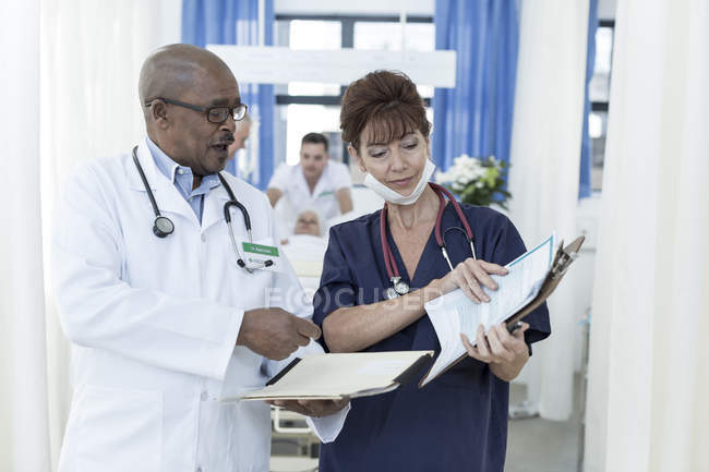 Two doctors with clipboards in hospital talking in corridor — Stock Photo