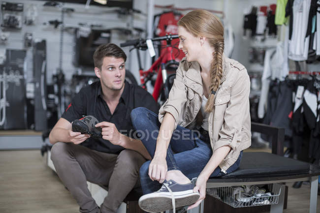 Young woman buying bicycle shoes, salesman advising — Stock Photo
