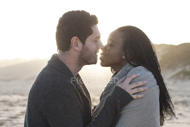 Young  couple kissing on the beach at sunset — Stock Photo