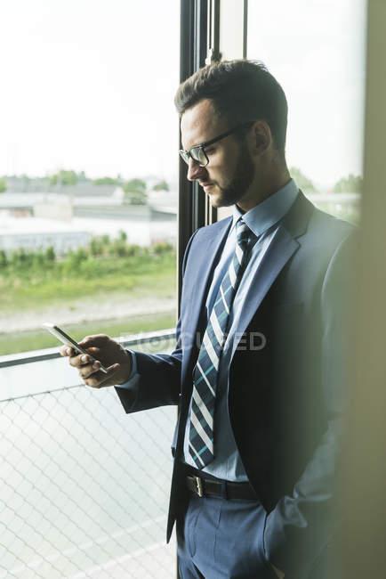 Jeune homme d'affaires à la fenêtre regardant sur le téléphone portable — Photo de stock