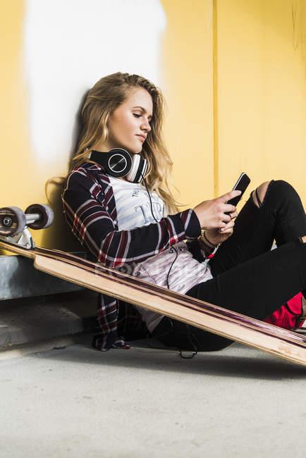 Adolescente, assis sur le sol avec la planche à roulettes et téléphone portable — Photo de stock