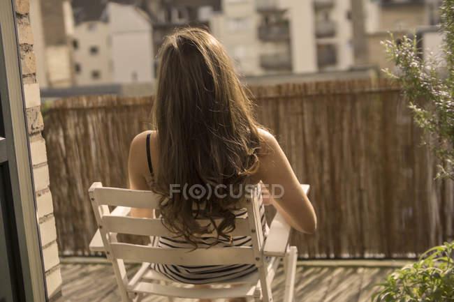Young woman sunbathing on balcony — Stock Photo