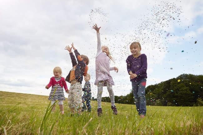 Niños pequeños lanzando confeti en el prado en el campo - foto de stock