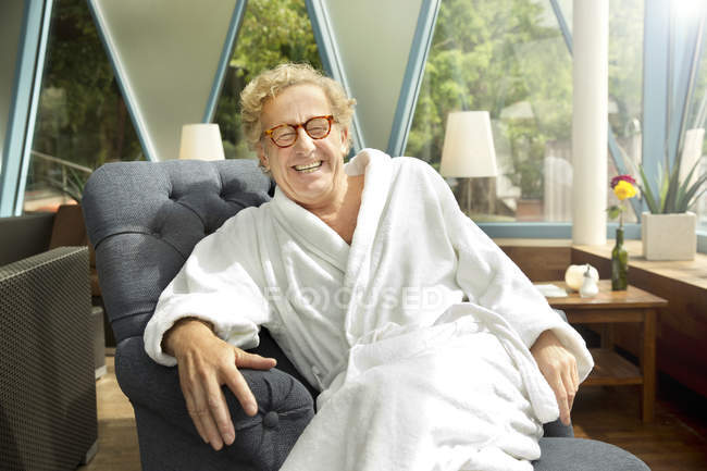 Laughing senior man in bathrobe sitting in armchair — Stock Photo