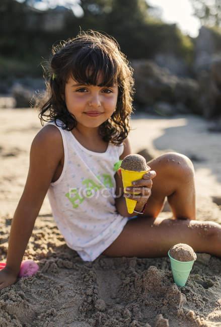 Портрет маленькой девочки, играющей с песком на пляже — стоковое фото
