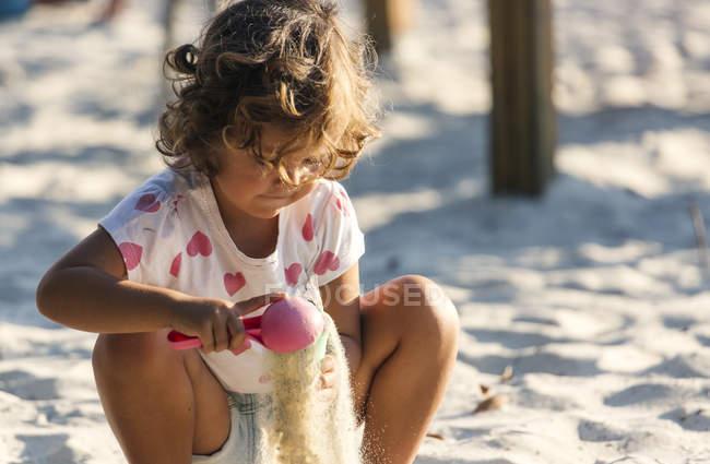 Little girl playing in sandbox on playground — Stock Photo
