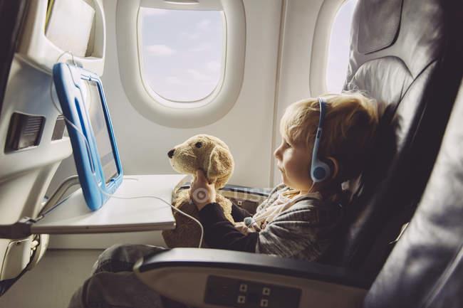 Niño, sentado en un avión viendo algo sobre tableta digital - foto de stock