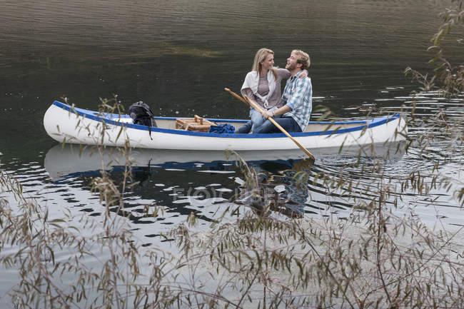 Jeune couple de détente dans un canot sur un lac — Photo de stock