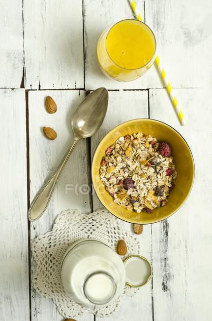 Миска фрукти мюслі, скло, манго пюре, ложка, пляшка молока — стокове фото
