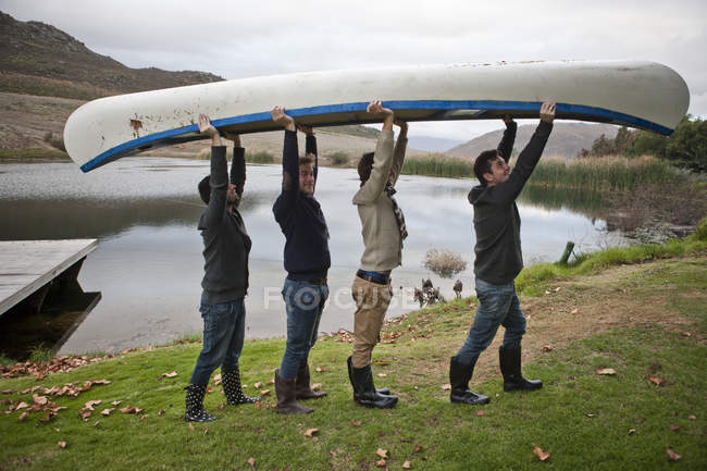 Quatre amis transportant un canot devant un lac — Photo de stock