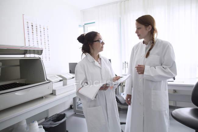 Techniciens de laboratoire avec revue en laboratoire — Photo de stock