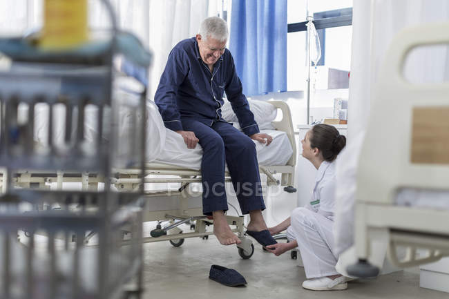 Nurse caring for senior patient in hospital bed — Stock Photo