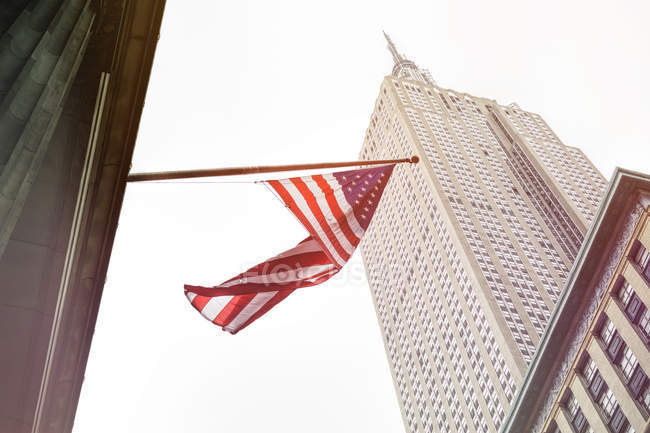 США, Нью-Йорку, Емпайр Стейт Білдінг з американським прапором на передньому плані — стокове фото