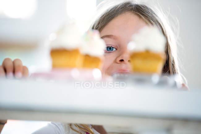 Девушка выглядит жадной через чашки тортов — стоковое фото