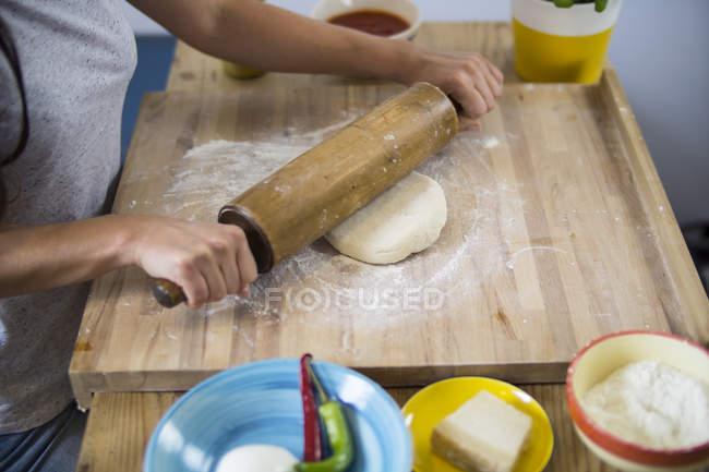 Woman preparing pizza dough in kitchen — Stock Photo