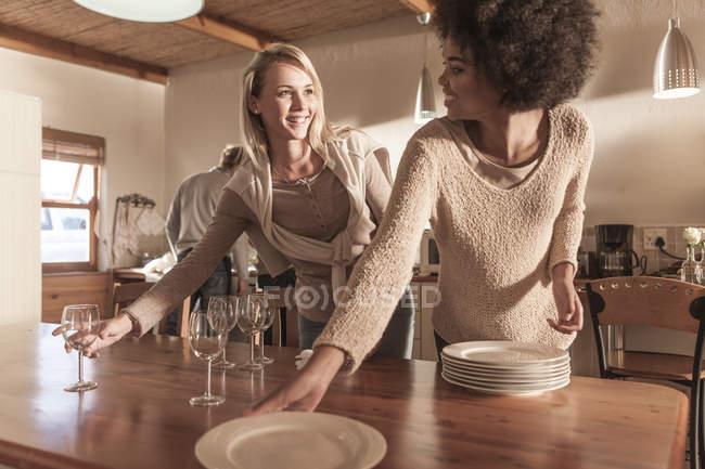 Две женщины вместе накрывают стол на современной кухне — стоковое фото