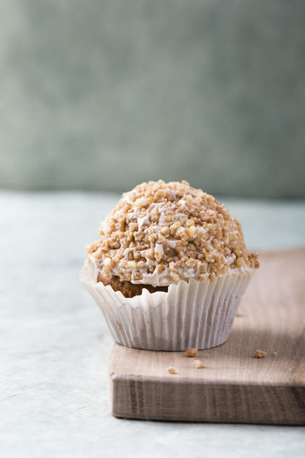 Cupcake with mocha cream and hazelnut brittle on wooden board — Stock Photo