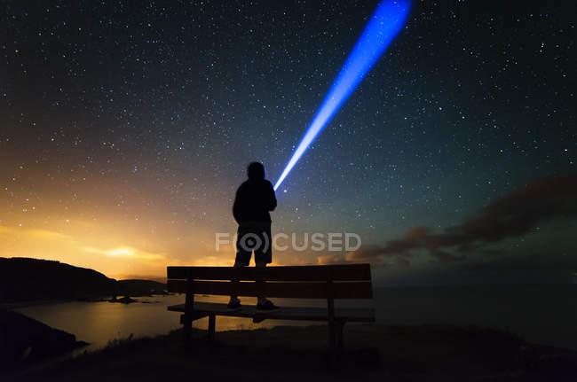 Spagna, Ortigueira, Loiba, sagoma di un uomo in piedi sul banco sotto un cielo stellato con Blu ray — Foto stock