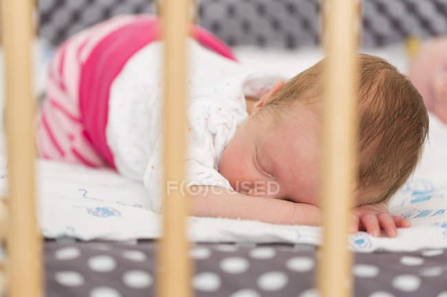 Новорожденный ребенок девочка спит на кровати — стоковое фото