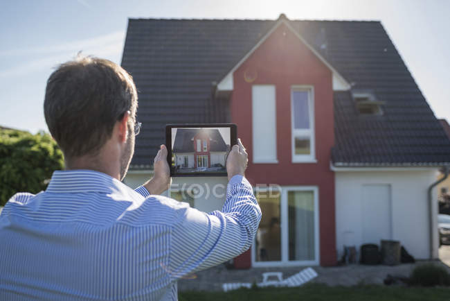 Man photographing his house with digital tablet — Stock Photo