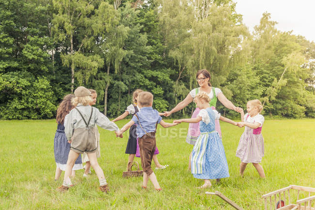 Kids and teacher doing ring-a-ring-a-roses on meadow — Stock Photo