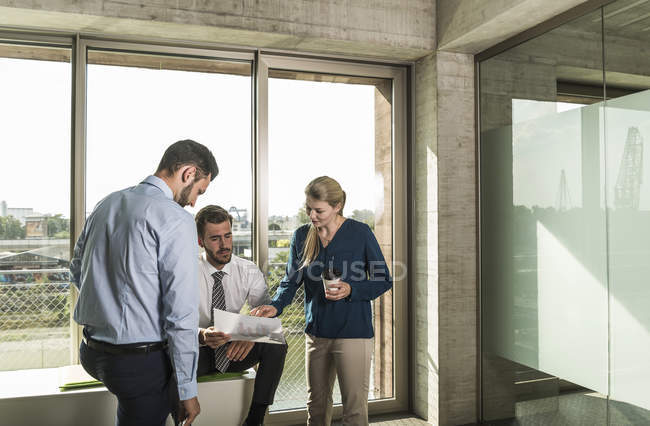 Three young business people discussing document in office — Stock Photo