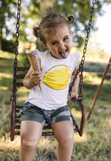 Портрет маленькой девочки с вытянутым языком, сидящей на качелях и поедающей мороженое — стоковое фото