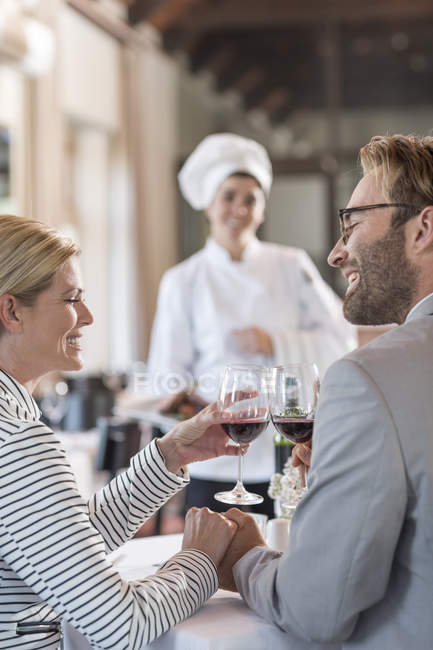 Mid adult couple in restaurant toasting with redwine — Stock Photo