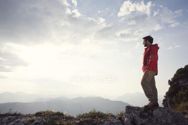 Austria, Tyrol, Unterberghorn, hiker standing in alpine landscape looking at view — Stock Photo