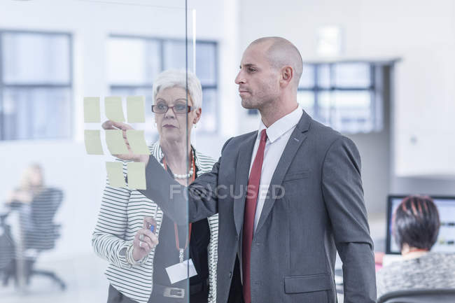 Colleagues discussing sticky notes on glass screen — Stock Photo