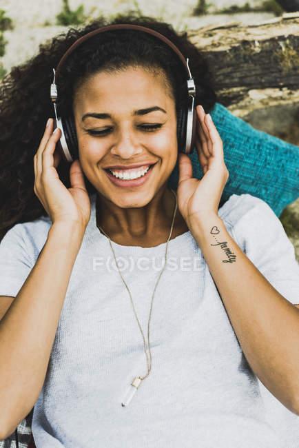 Sorrindo jovem com fones de ouvido ao ar livre — Fotografia de Stock