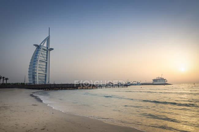 Объединенные Арабские Эмираты, Дубай, закат на пляже Джумейра с Бурдж аль Араб и Джумейра Бич Отель — стоковое фото