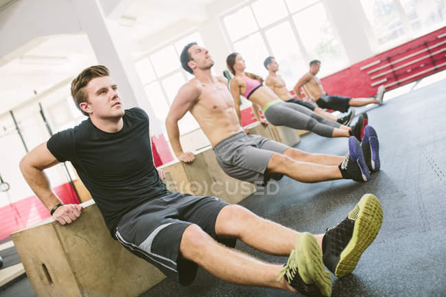 Crossfit athletes doing box dips in gym — Stock Photo