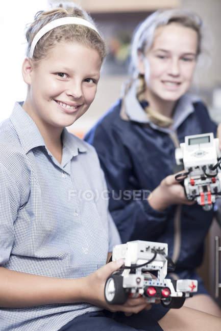 Дві школярки в класі робототехніки, представляючи транспортних засобів — стокове фото