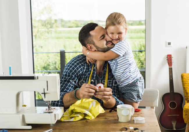 Bonne fille câlinant père à la maison — Photo de stock