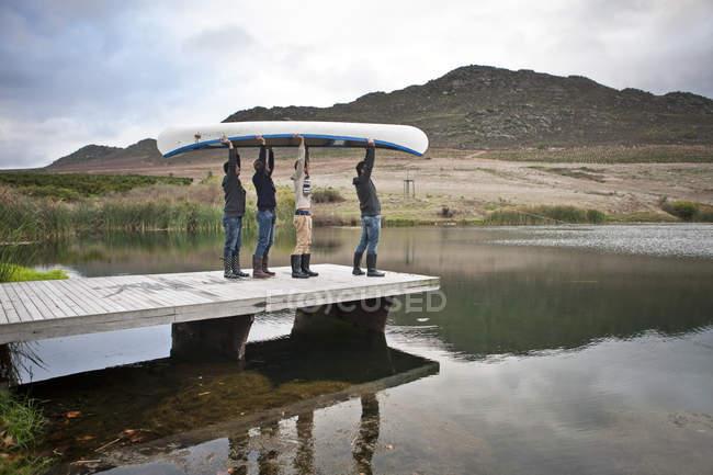 Quatre amis transportant un canot au lac — Photo de stock