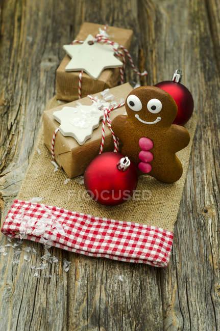 Hombre actual, pan de jengibre de Navidad y dos adornos de Navidad rojo - foto de stock