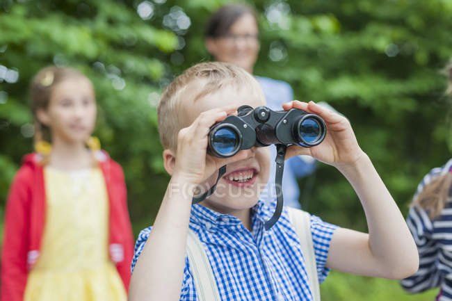 Close-up of boy with binoculars watching in nature — Stock Photo