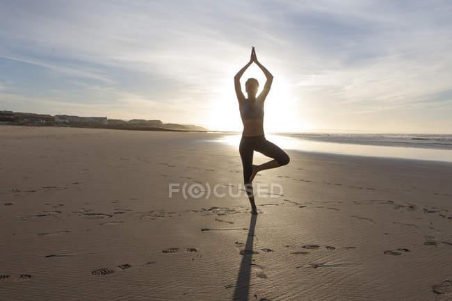 Южная Уфа, Кейптаун, силуэт молодой женщины, делающей упражнения на растяжку на пляже при подсветке — стоковое фото